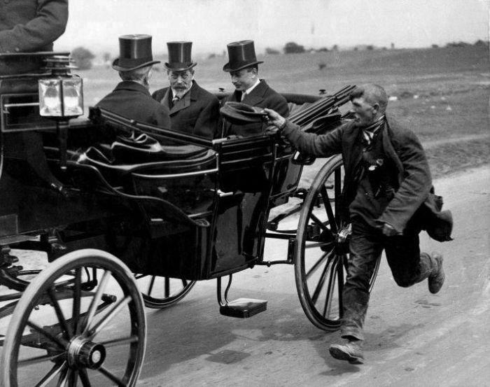Beggar holding out his cap as he passes King George V in a carriage, c1911-1936.